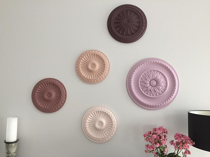 Stuckrosetten aus Styropor an der Wand in unterschiedlichen Farben